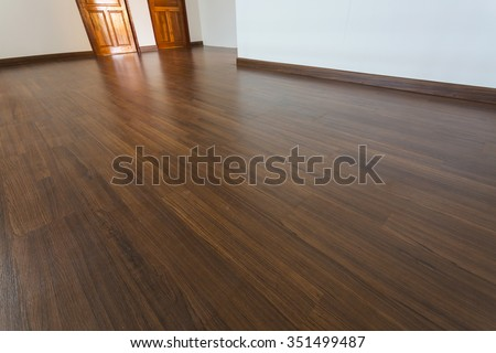 empty room, white mortar wall background and wood laminate floor in residential - stock photo