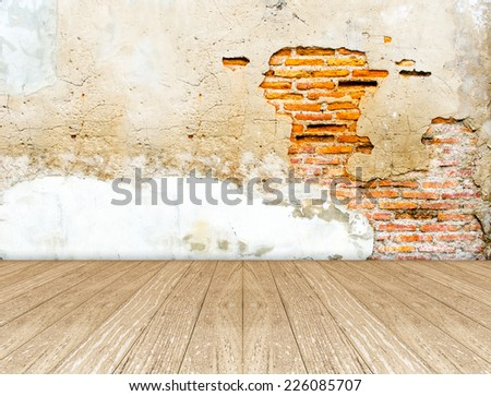 Empty room  with crack brick wall and wooden floor - stock photo