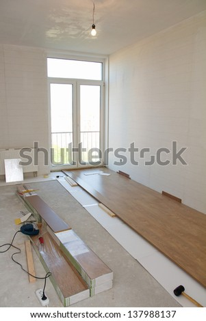 Empty room with laminate flooring and tools - stock photo