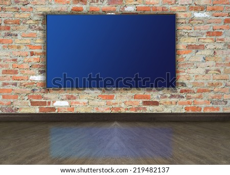 Empty room with tv on brick wall. - stock photo