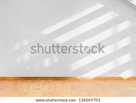 Empty room with wooden floor and diagonal shadows on white wall - stock photo