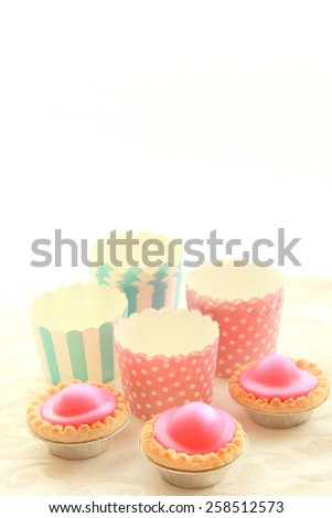 Empty round muffin cups and pink cakes - stock photo