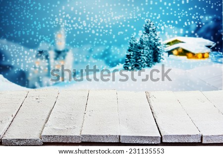 Empty rustic white painted wooden table with rough boards against a winter Christmas scene of a log cabin and church in snowy mountain scenery with glowing windows for product placement - stock photo