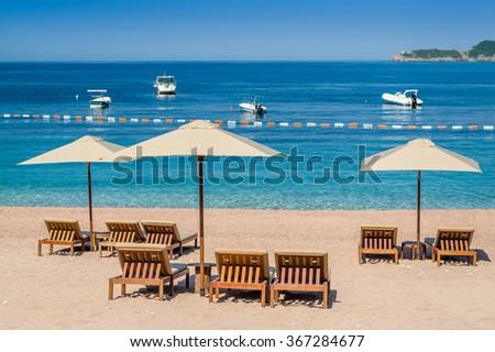 Empty sand beach with wooden furniture and perfect Adriatic sea. Budva, Montenegro. - stock photo