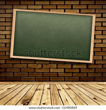 Empty school blackboard at brick wall in interior with wooden floor - stock photo