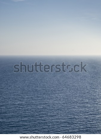 Empty seascape showing the blue sea, the horizon line and the blue summer sky - stock photo