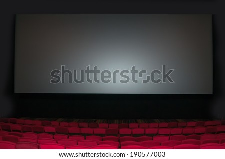 Empty seat on row in thearter with movie screen - stock photo