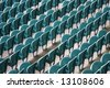 Empty Seating at Sports Stadium with Green Chairs - stock photo
