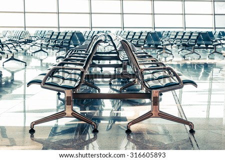 Empty seats in the departure lounge at the airport - stock photo
