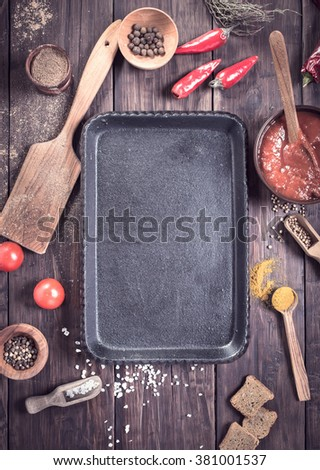 Empty serving pan and various cooking ingredients and spice among. Top view - stock photo