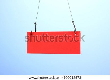 Empty sheet of a paper on fish hooks on blue background - stock photo