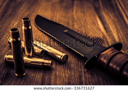 Empty shells from the rifle and combat knife lying on a wooden table. Focus on the shells, image vignetting and the yellow-blue toning - stock photo