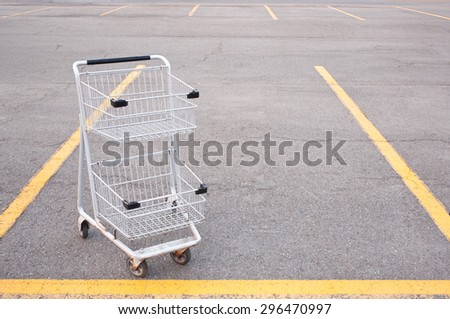 Empty shopping cart in empty parking lot. - stock photo