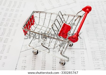 Empty shopping cart on a financial report - stock photo