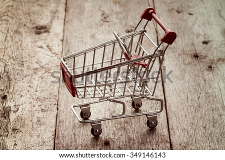 Empty shopping cart on the wooden surface.Vintage filter. - stock photo