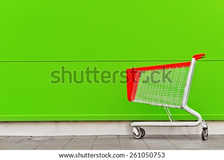 Empty Shopping Cart Trolley in front of Shopping Mall with Blank Copy Space as Consumerism Concept Background. - stock photo