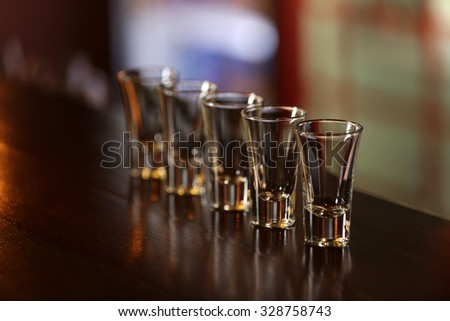 Empty shot glasses on bar counter  - stock photo