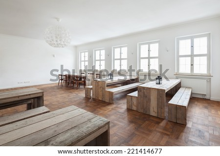 Empty simple rustic wooden benches and tables in a bright white commercial canteen interior with a parquet floor and row of windows - stock photo