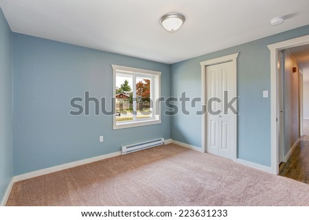Empty small room with light blue walls and brown carpet floor. Room has closets - stock photo
