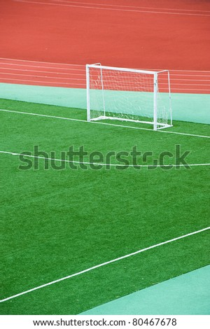 Empty soccer field with goal posts and light poles. - stock photo