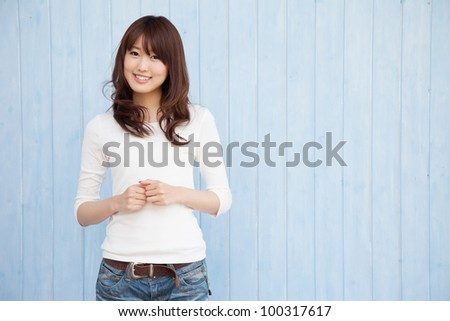 Empty space and a young Asian woman smiling blue background - stock photo