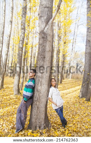 Empty Space for inscription Young latin hispanic full length couple behind a tree an autumn symbol of quarrels misunderstandings depression divorce and separation hurt parting  - stock photo