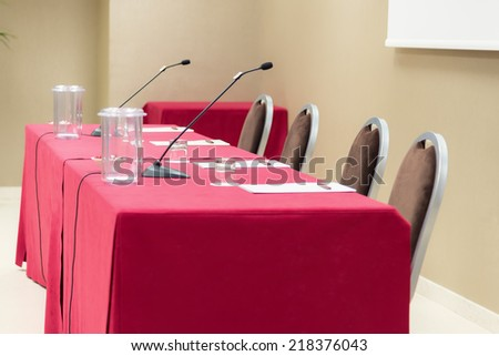 empty speaker conference table with microphones - stock photo