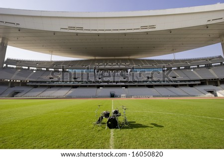 Empty stadium and the drum set on green grass soccer field - stock photo