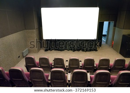 Empty stage in the small movie theater with white isolated screen - stock photo
