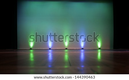 Empty Stage with a Blank Screen, highlighted by colorful stage lighting. Plenty of empty screen space for copy text. - stock photo