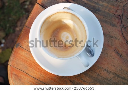 Empty stain coffee in white cup.Milk stain coating on wood table. - stock photo