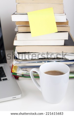 Empty Sticky Note Paper on Book Stack in Office Environment - stock photo