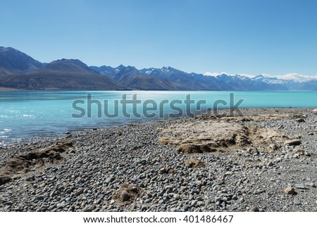 empty stone beach near clean water and snow mountains in blue sky in new zealand - stock photo