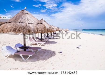Empty straw huts by the beach in Mexico - stock photo