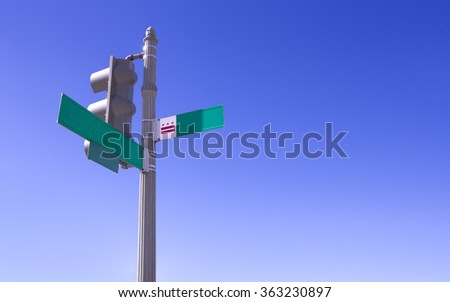 Empty street sign and traffic light over deep blue sky.  - stock photo