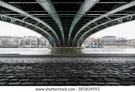 Empty street under a bridge in Lyon on a grey, winter day in February. - stock photo