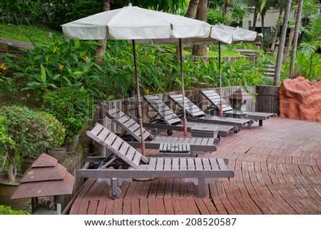 Empty sunbeds by the resort pool. - stock photo