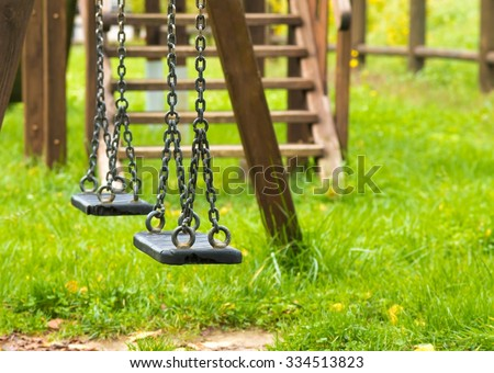 empty swings at playground for child, on green meadow background - stock photo