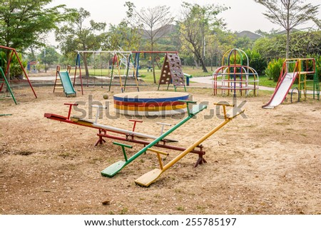 Empty swings on summer kids playground - stock photo