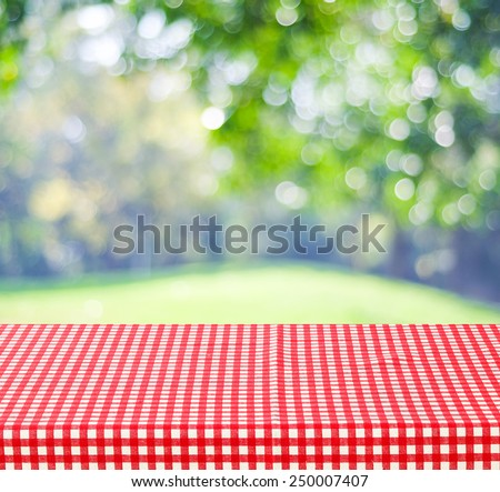 Empty table and red tablecloth over blur tree and bokeh background, for product display montage - stock photo