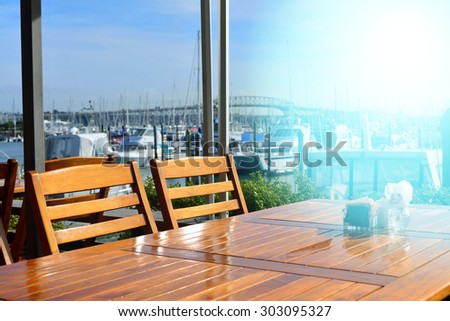 Empty table at a waterfront cafe in the morning - stock photo
