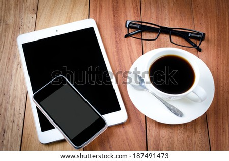empty tablet and a cup of coffee on the wooden desk background - stock photo