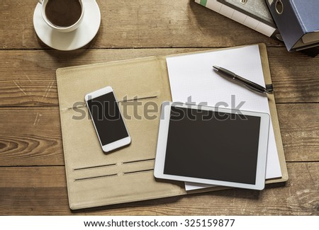 empty tablet and phone lying on an office folder - stock photo