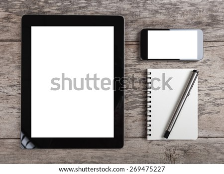 empty tablet and smart phone with note paper  on the wooden table - stock photo