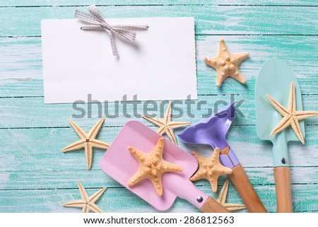 Empty tag and tools for children for playing in sand, sea object on turquoise  painted wooden planks. Place for text. Vacation, holiday, summer background.  - stock photo