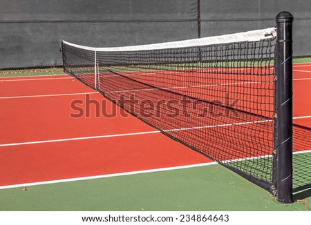 Empty tennis court and net, low angle, perspective view. Black nylon rope net tied to metal pole. Red and green clay surface. Gray canvas wall in background.  - stock photo