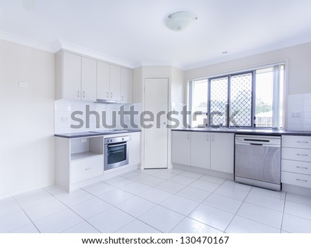 Empty tiled kitchen with dish stainless steel appliances - stock photo