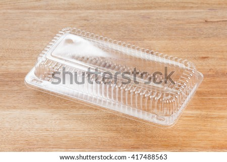 Empty transparent plastic storage box of food package on wooden background - stock photo