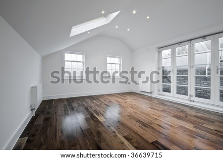 empty unfurnished loft room with roof window and solid wood floor - stock photo