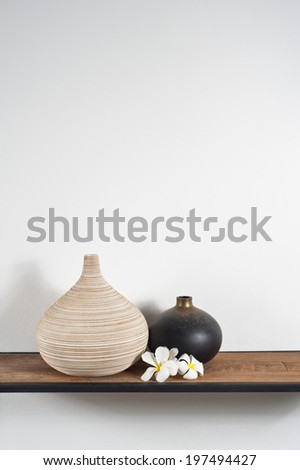 Empty vases decorated with Frangipani flower over side board - stock photo
